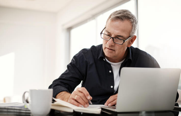 A man computing his taxes while opening his laptop and having his coffee