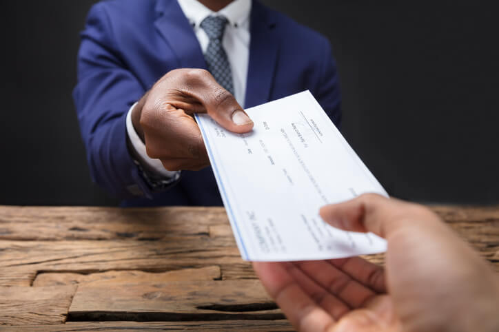 A person in a suit handing out cheques